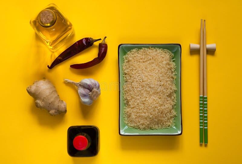 Aziatische voedselingrediënten, kruiden en sausen op een gele achtergrond Het concept de populairste Chinese schotels, exemplaarr royalty-vrije stock fotografie