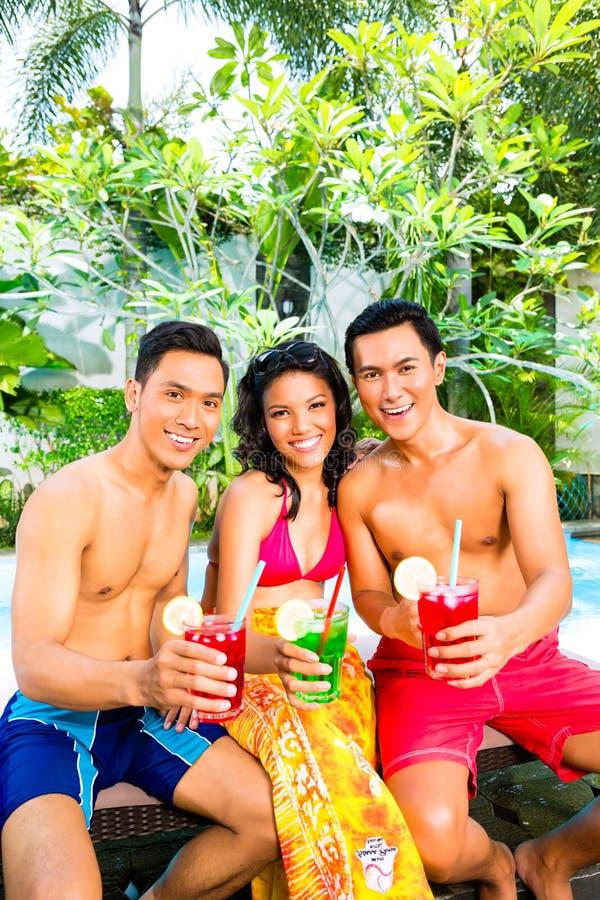 Aziatische vrienden die cocktails drinken bij pool stock foto's
