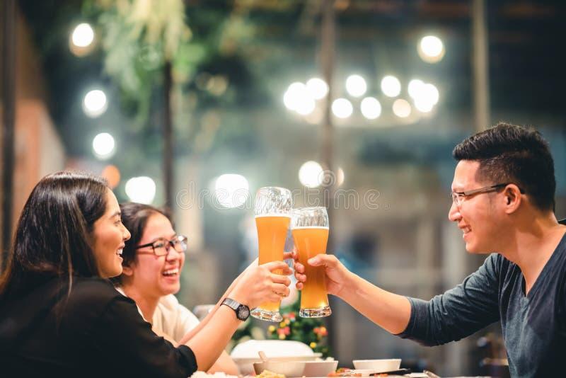 Aziatische vrienden of medewerkers die met bier toejuichen, samen vierend bij restaurant of nachtclub Jongeren die bij partij roo royalty-vrije stock afbeelding