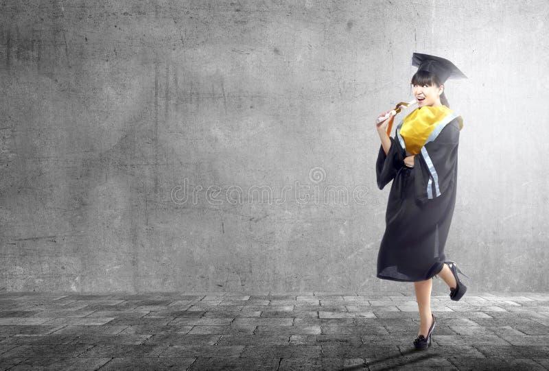 Aziatische vrouw in barethoed en diploma die van universiteit een diploma behalen stock afbeeldingen