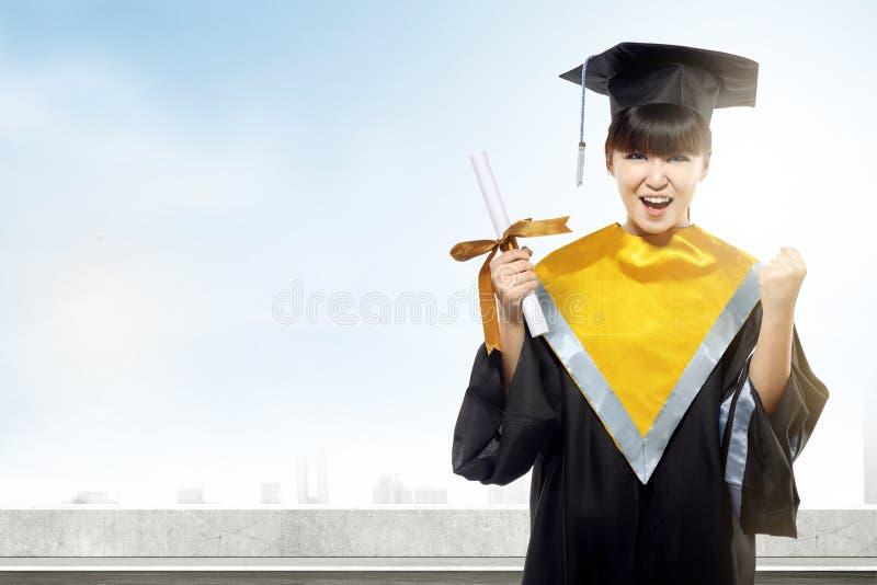 Aziatische vrouw in barethoed en diploma die van universiteit een diploma behalen stock fotografie