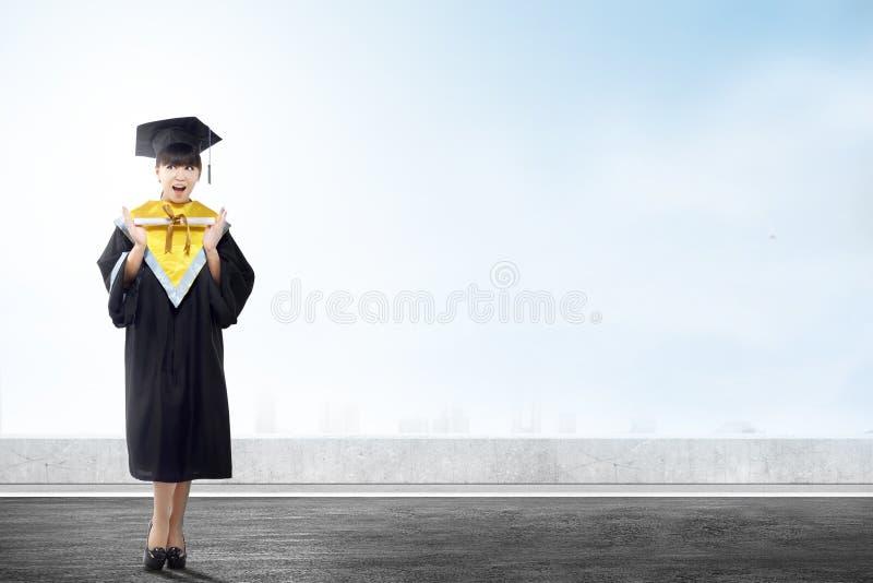 Aziatische vrouw in barethoed en diploma die van universiteit een diploma behalen royalty-vrije stock fotografie