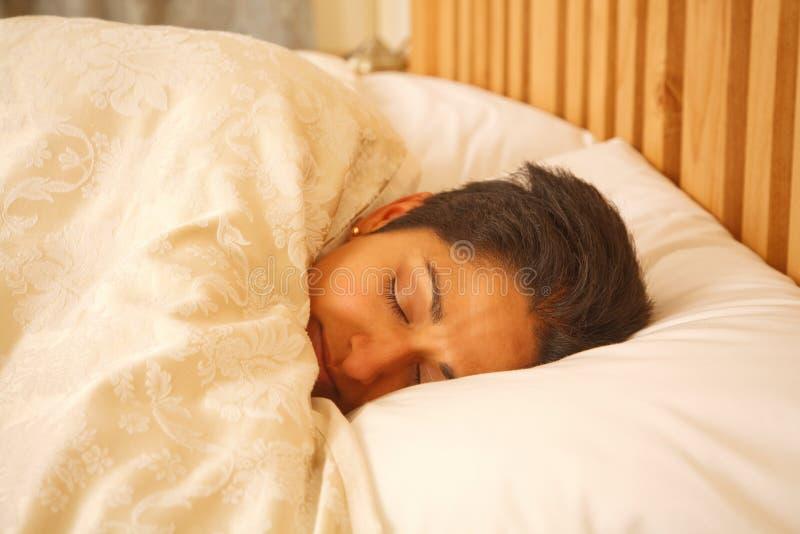 Aziatische vrouw in bed stock afbeeldingen