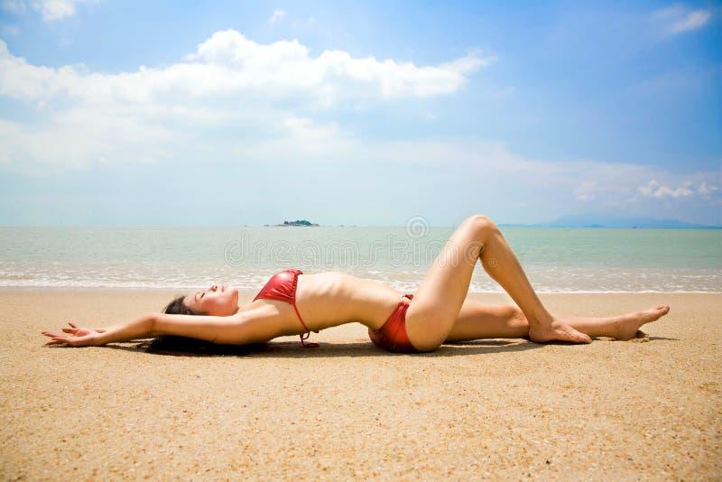 Aziatische vrouw in bikinihelling op het de zomerstrand stock foto