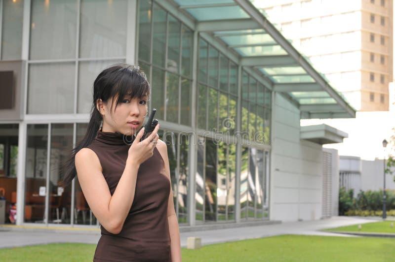 Aziatische Vrouw in de Stad die een walkie-talkie met behulp van stock foto's
