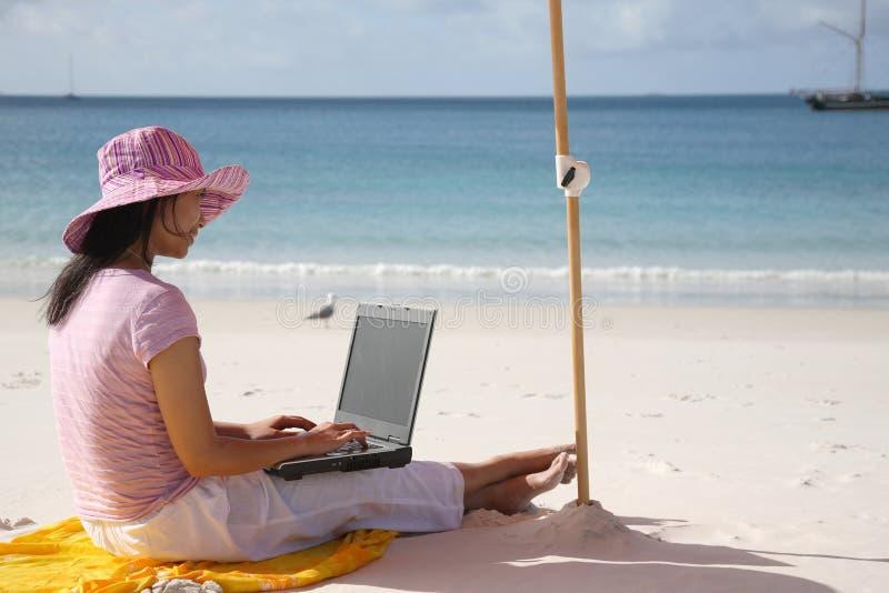 Aziatische Vrouw die aan het strand werkt royalty-vrije stock afbeelding