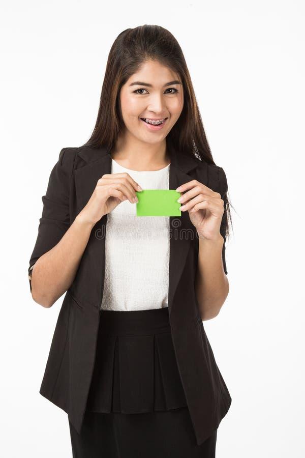 Aziatische Vrouw die in bedrijfs formeel zwart kostuum een groene lege naamkaart houden stock afbeelding