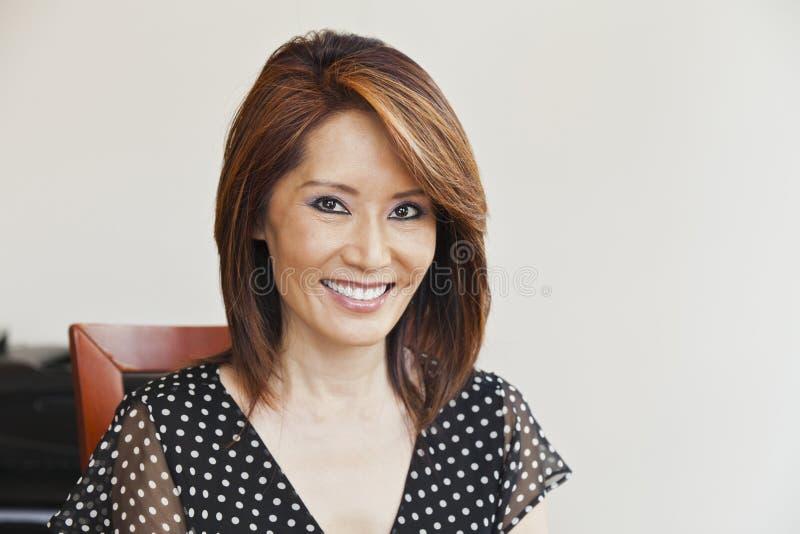 Aziatische vrouw die bij haar bureau glimlachen royalty-vrije stock afbeeldingen