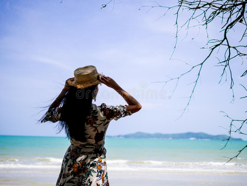 Aziatische vrouw die Boheemse kledingsstijl met hoed dragen die zich bij kust bevinden die aan witte strand en golf met blauwe he stock afbeelding