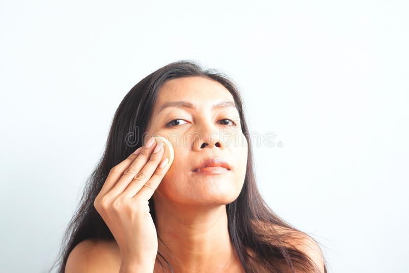 Aziatische vrouw die camera bekijken en stichtingspoeder op haar gezicht toepassen schoonheid royalty-vrije stock afbeeldingen