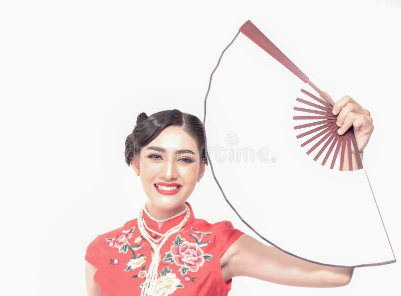Aziatische vrouw die in Chinese rode traditionele kleding een witte lege ventilator met het mooie glimlachen op witte achtergrond royalty-vrije stock foto's