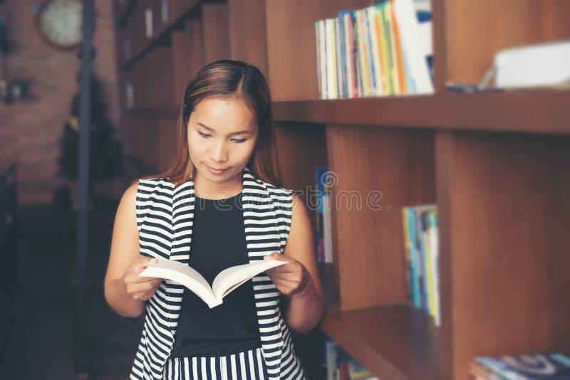 Aziatische vrouw die een boek in bibliotheek lezen royalty-vrije stock afbeelding