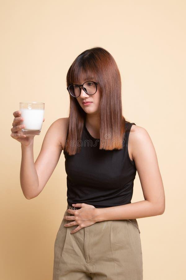 Aziatische vrouw die een glas van melk geworden maagpijn drinken royalty-vrije stock afbeeldingen