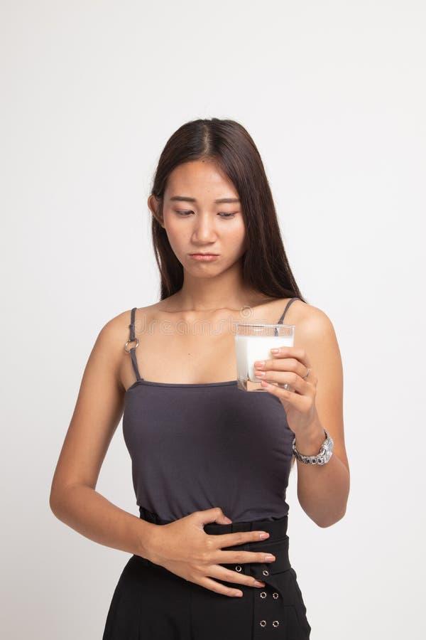 Aziatische vrouw die een glas van melk geworden maagpijn drinken royalty-vrije stock foto