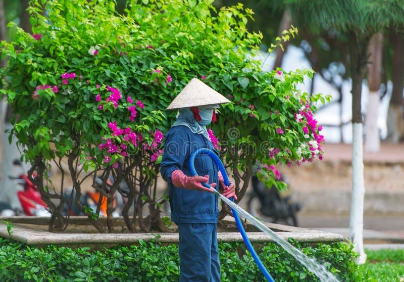 Aziatische vrouw die een groene en bloementuin in de voorstad van Nha Trang water geven royalty-vrije stock afbeeldingen