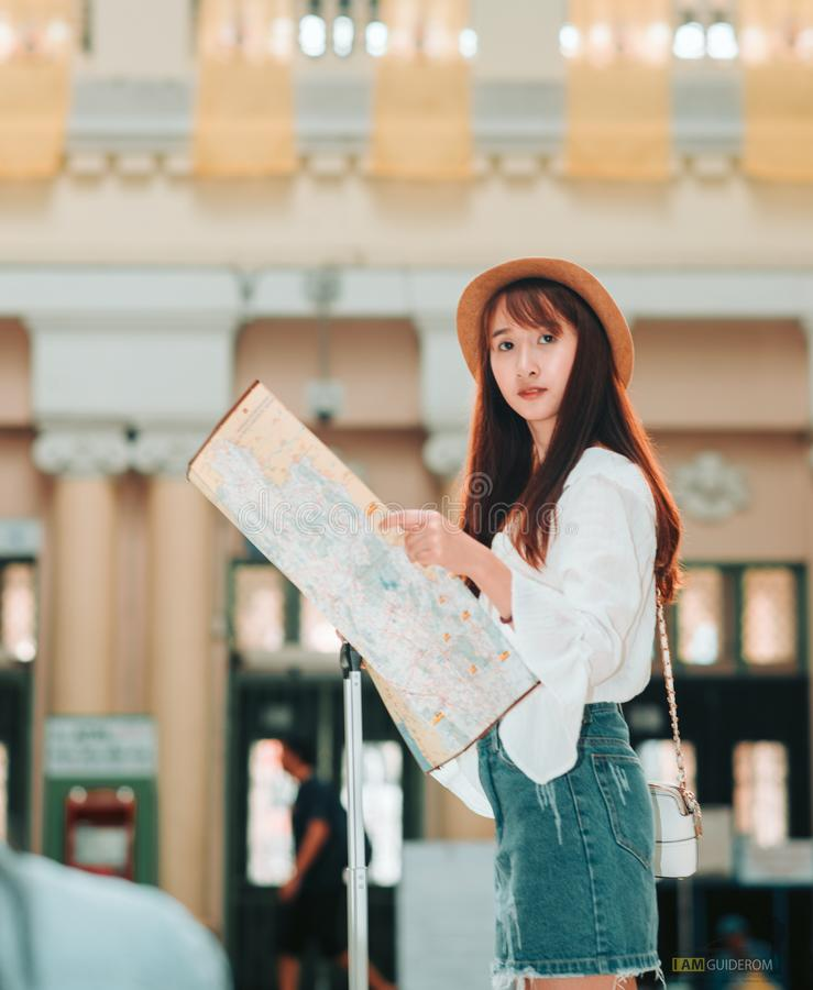 Aziatische vrouw die een kaart bewaarde die een plek zoekt om te reizen royalty-vrije stock afbeelding