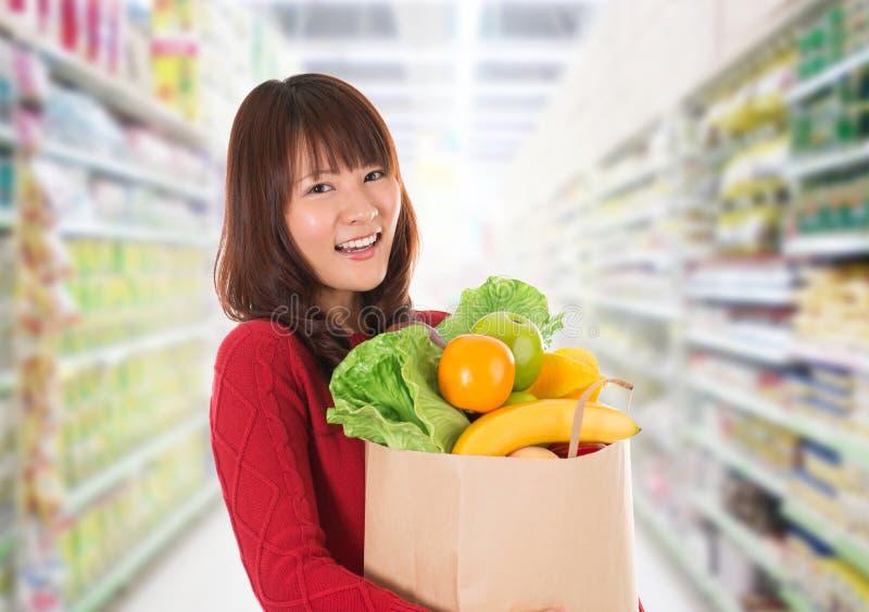 Aziatische vrouw die in een kruidenierswinkelopslag winkelen royalty-vrije stock afbeelding