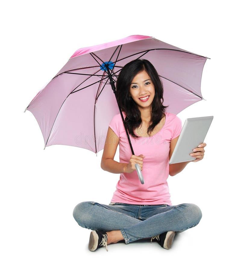 Aziatische vrouw die een paraplu en een tabletpc houden terwijl het zitten royalty-vrije stock foto