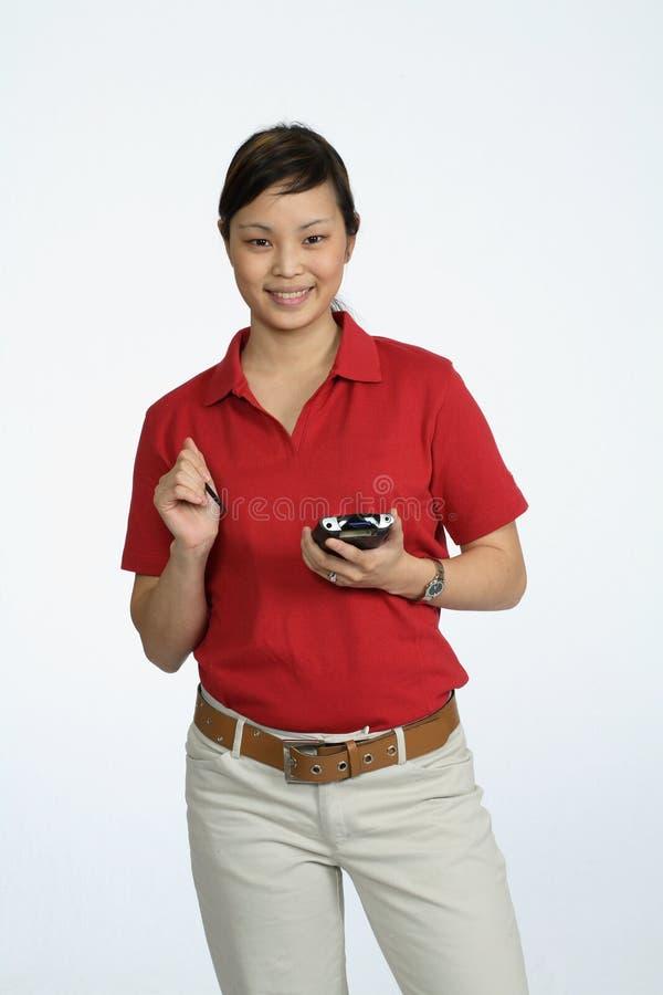 Aziatische vrouw die een PDA gebruikt stock fotografie