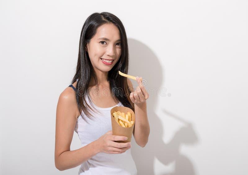Aziatische Vrouw die frieten eten stock afbeelding