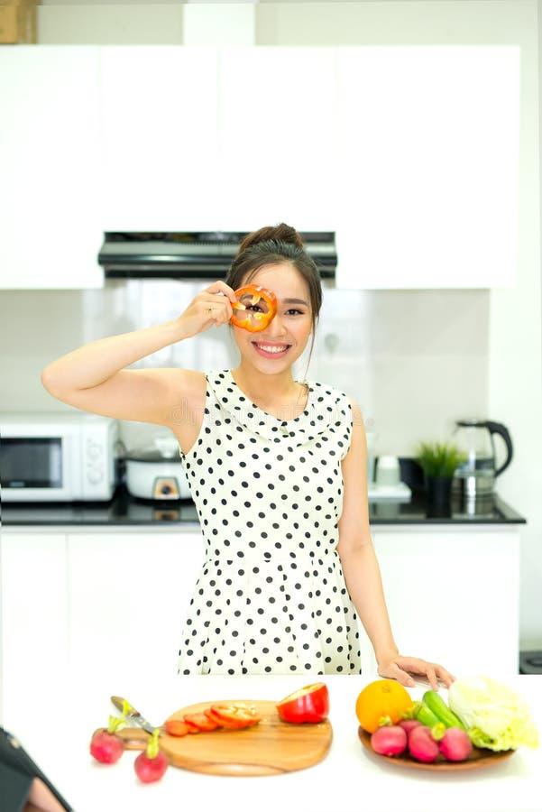 Aziatische vrouw die gezonde maaltijd in haar huiskeuken voorbereiden stock afbeelding