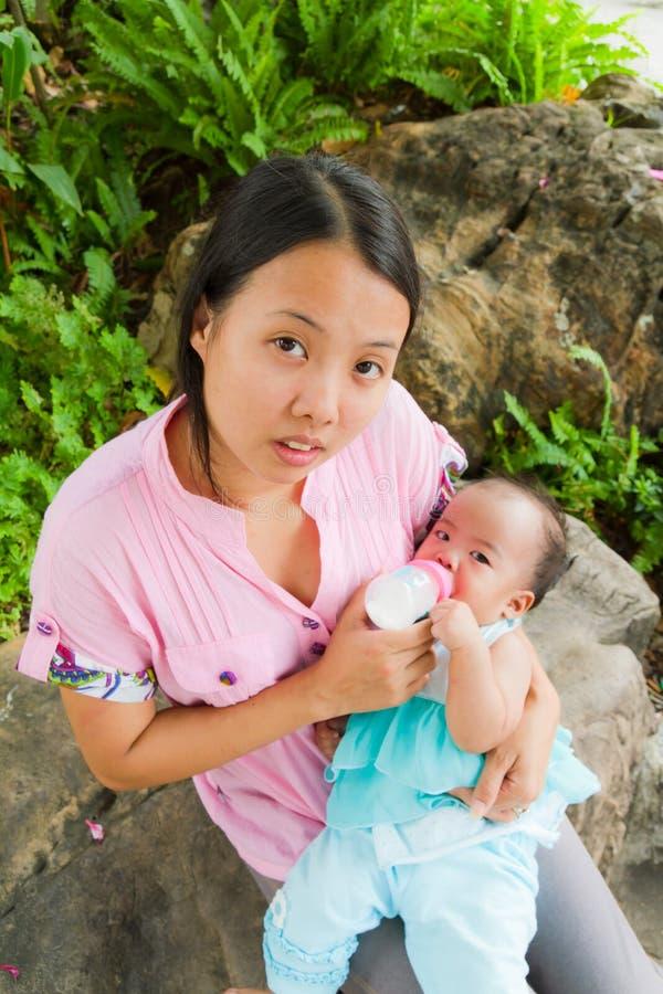 Aziatische vrouw die haar baby hoogste verticaal voedt royalty-vrije stock afbeelding