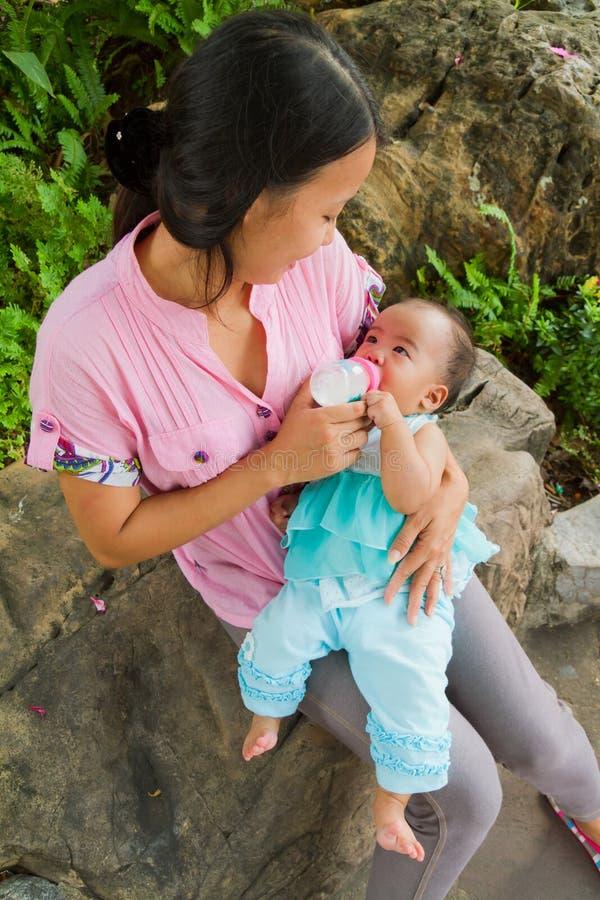 Aziatische vrouw die haar baby hoogste verticaal voedt royalty-vrije stock foto's