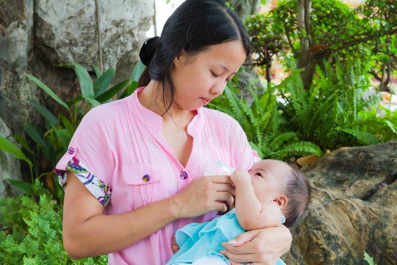 Aziatische vrouw die haar baby in park voedt royalty-vrije stock fotografie