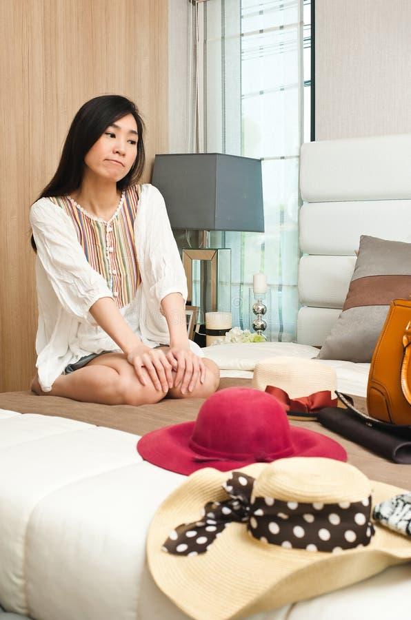 Aziatische vrouw die haar manieruitrusting kiezen Mooi wijfje die welke hoed en zak denken om in gedesorganiseerde punten op bed  stock foto's