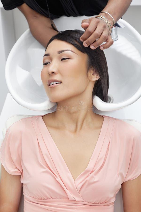 Aziatische vrouw die haarwas hebben bij schoonheidssalon stock fotografie