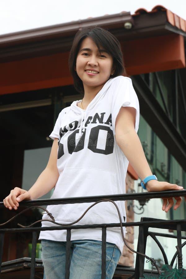 Aziatische vrouw die in het park glimlacht stock fotografie