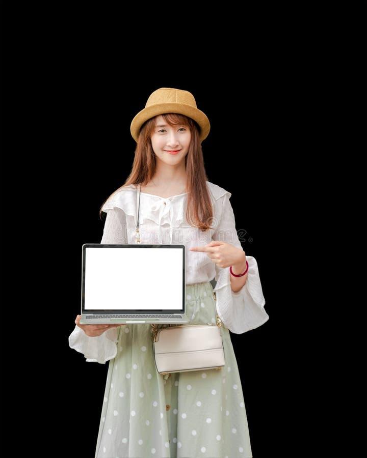 Aziatische vrouw die laptop vasthoudt is wit scherm, zwarte achtergrond royalty-vrije stock foto