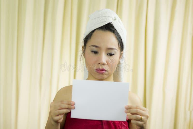 Aziatische vrouw die lege lege banner en acteren houden zij draagt een rok om haar die borst na washaar te behandelen, in Handdoe stock foto