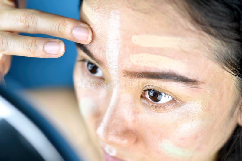 Aziatische vrouw die make-up, Schoonheidsmiddelenstichting toepassen gebruikend aan het verbeteren of verbergend gezichtshuidprob royalty-vrije stock foto's