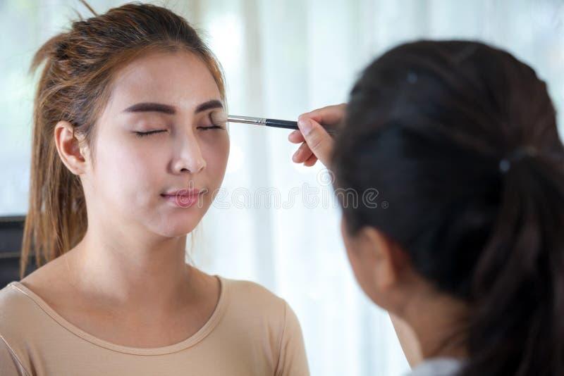 Aziatische vrouw die mascara op haar lange wimpers toepassen stock foto's