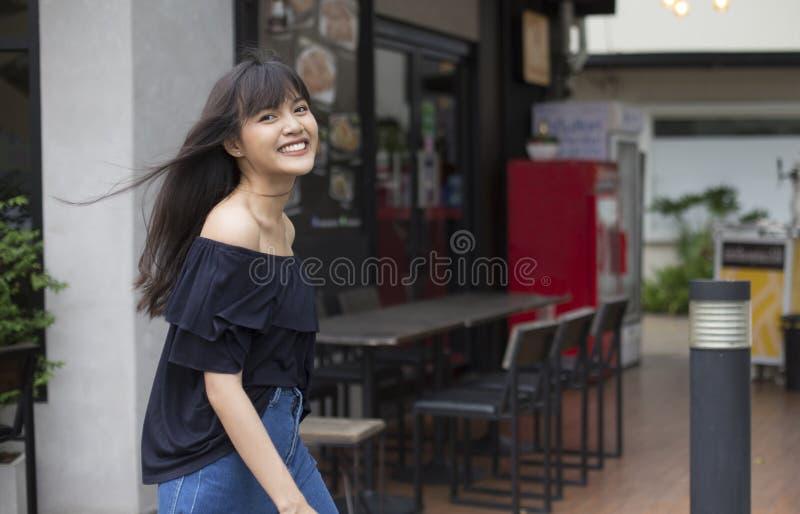 Aziatische vrouw die met gelukkig op restaurantachtergrond lopen stock afbeelding