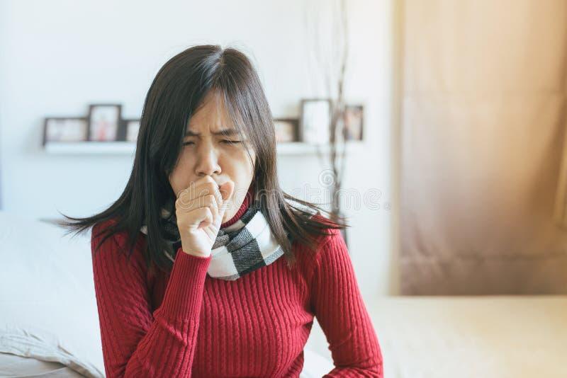 Aziatische vrouw die met keelpijn, Wijfje hoesten die met hoest aan een partij in slaapkamer lijden stock foto's