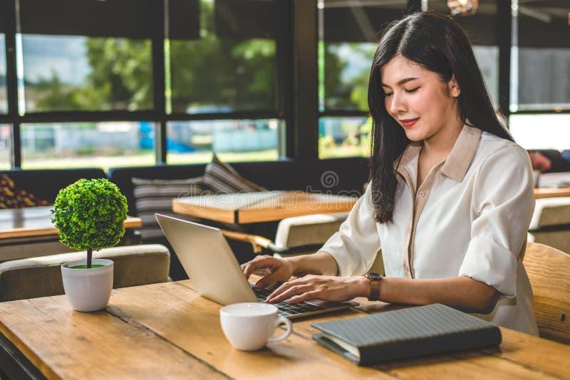 Aziatische vrouw die met laptop in koffiewinkel werken Mensen en levensstijlenconcept In openlucht het werken en freelance thema royalty-vrije stock foto's