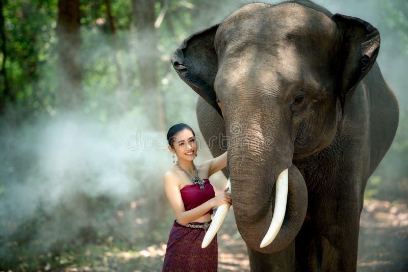 Aziatische vrouw die met olifant bij Chang Village Surin-provin genieten van royalty-vrije stock foto