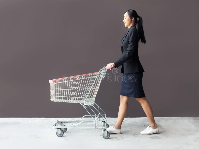 Aziatische vrouw die met troleykar winkelt royalty-vrije stock afbeeldingen