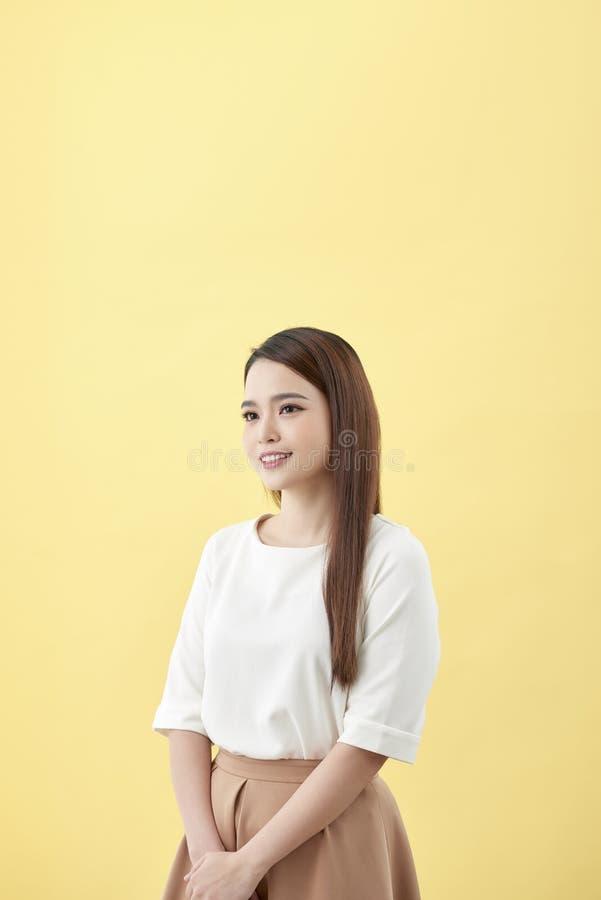 Aziatische vrouw die met zwarte ogen van het kuiltje de lange haar op gele achtergrond glimlachen royalty-vrije stock afbeeldingen