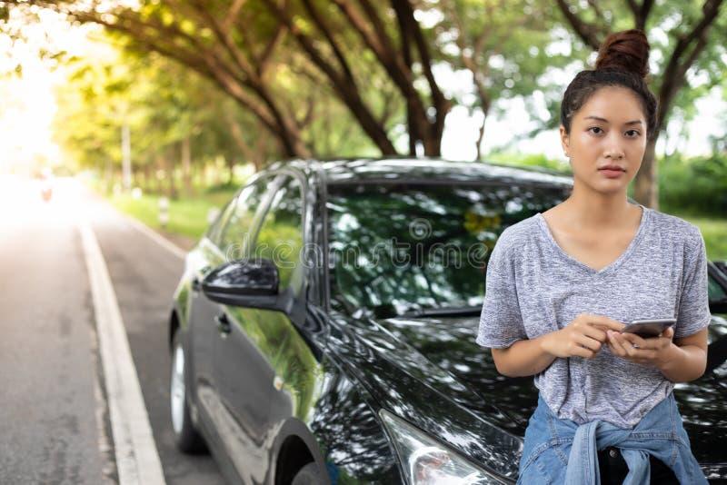 Aziatische vrouw die mobiele telefoon met behulp van terwijl het kijken en Beklemtoond man Si stock fotografie