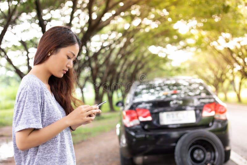 Aziatische vrouw die mobiele telefoon met behulp van terwijl het kijken en Beklemtoond man Si royalty-vrije stock fotografie