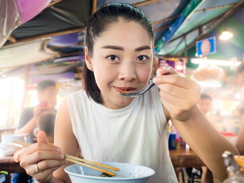 Aziatische vrouw die noedel in Thais lokaal restaurant eten royalty-vrije stock foto's