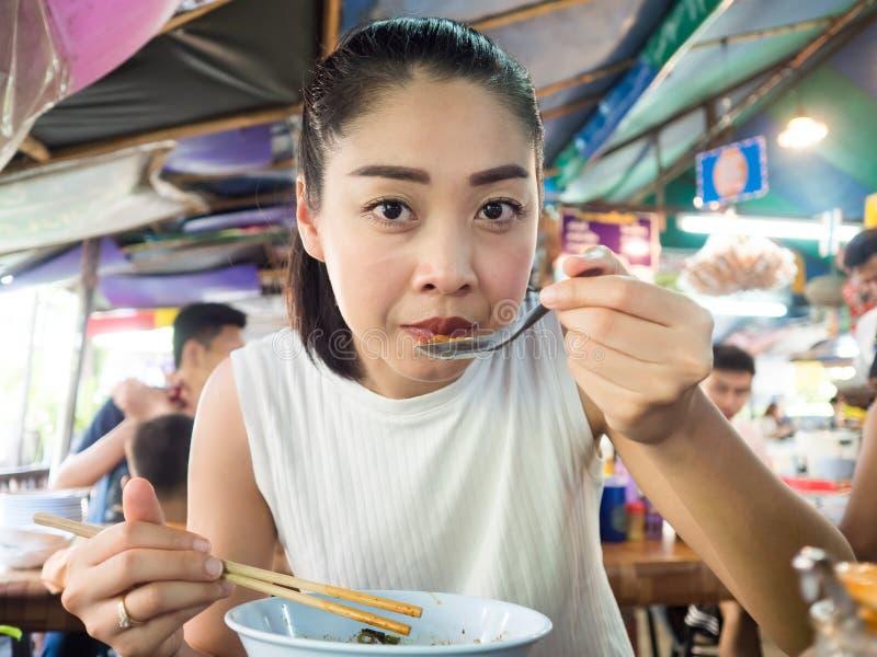 Aziatische vrouw die noedel in Thais lokaal restaurant eten royalty-vrije stock fotografie