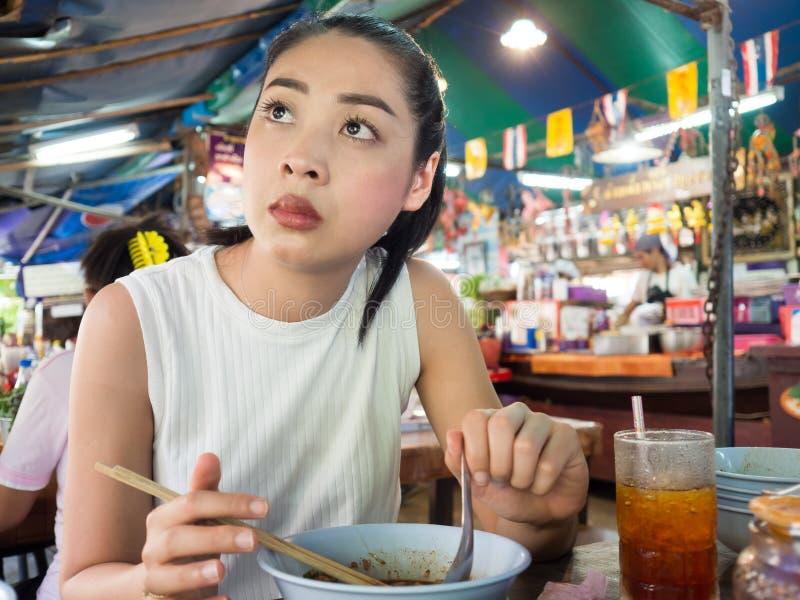 Aziatische vrouw die noedel in Thais lokaal restaurant eten stock foto's