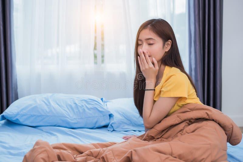 Aziatische vrouw die in ochtend in luie houding in slaapkamer thuis opstaan Mensenlevensstijlen en Gezondheidszorgconcept overnig royalty-vrije stock afbeeldingen