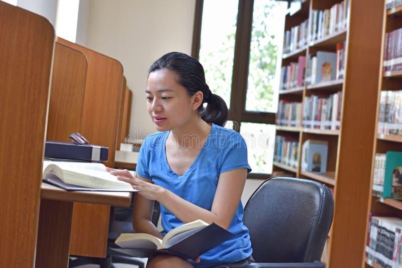 Aziatische vrouw die onderzoek doen en boek in bibliotheek lezen stock afbeeldingen