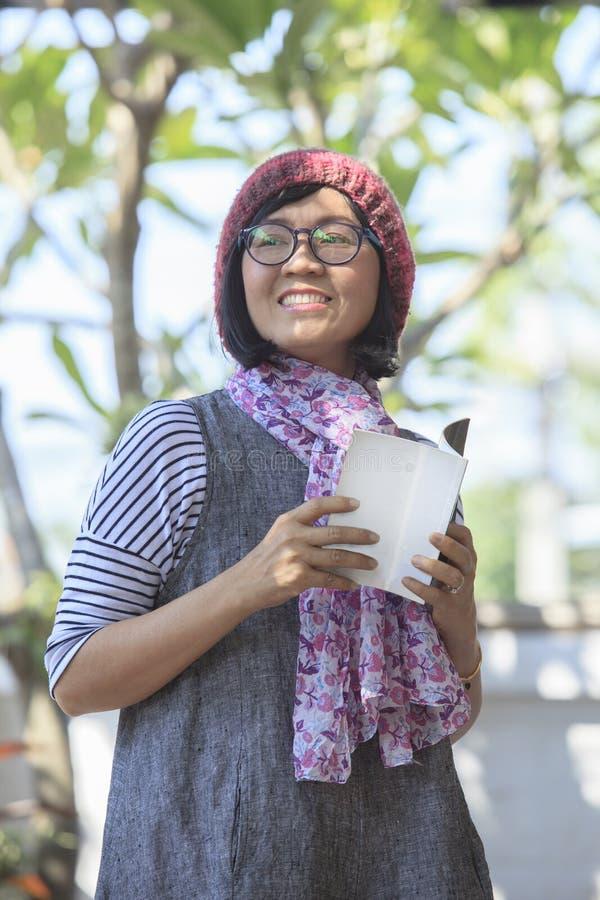 Aziatische vrouw die open booketboek houden het in hand en toothy glimlachen stock foto