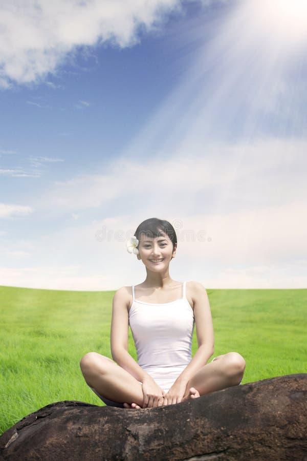 Aziatische vrouw die in openlucht op de rots bij weide tegen blauwe hemel mediteren royalty-vrije stock afbeelding